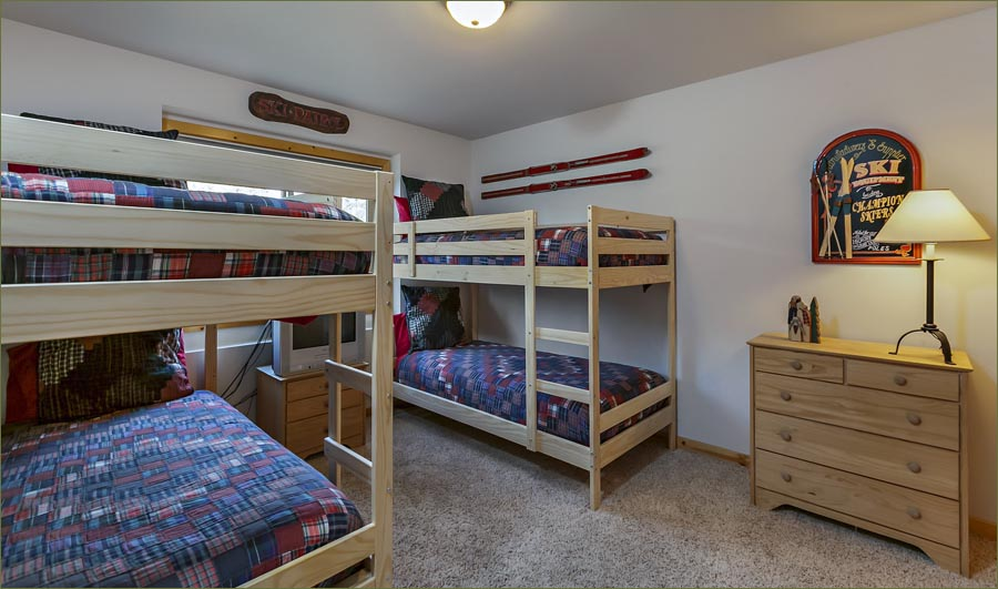 Bunk room two with comfortable bedding and full, shared bathroom upstairs.